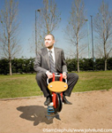 Funny picture of a businessman sitting on a playground spring rider of some sort. The man is way too big to fit on the children's playground equipment. The man is wearing a coat and tie and the sky is blue in the background.